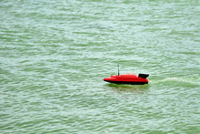 A Radio-controlled Toy Boat Floats On The Sea.