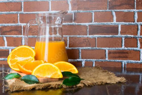 Fototapeta Orange juice in a jug on the background of the brick wall. obraz