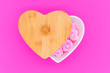 canvas print picture - Pink flowers in a heart-shaped casket with wooden lid against a pink background. Valentines day background.