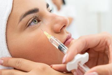 Kosmetolog wykonuje zabieg przeciwzmarszczkowy. Ostrzykiwanie toksyną botulinową, redukcja zmarszczek. Botoks w klinice medycyny estetycznej. Wstrzykiwanie wypełniacza pod oczy.