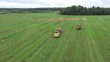Aerial Video. Rolling Haystacks In Countryside On The Field On A Cloudy Day. Tractor Loading Hay Bales On Truck Trailer During Agricultural Works.