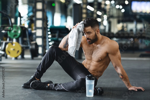 Obraz Handsome athlete wiping sweat after workout at gym - fototapety do salonu