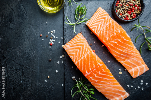 Fototapeta Raw salmon fillet and ingredients for cooking, seasonings and herbs on a dark background . Top view obraz
