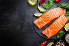 Raw Salmon Fillet And Ingredients For Cooking, Seasonings And Herbs On A Dark Background . Top View