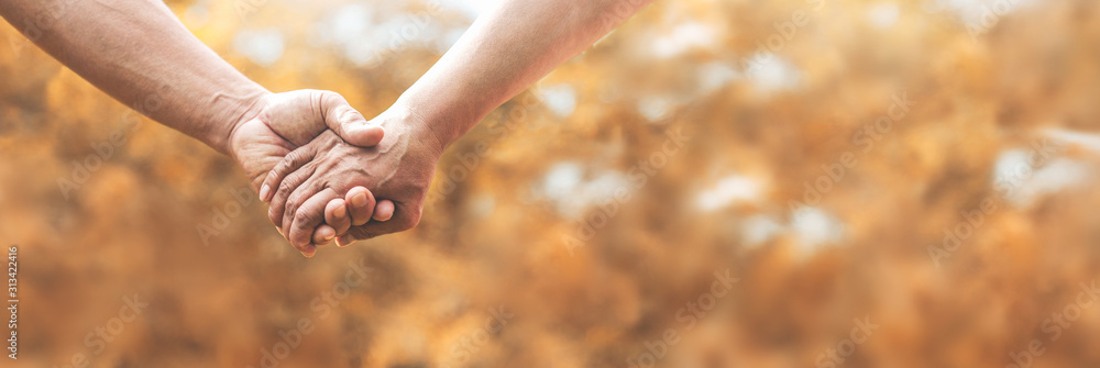 Fototapeta Loving Senior couple holding hands together over nature background.