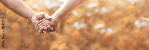 Senior couple holding hands together over nature background.