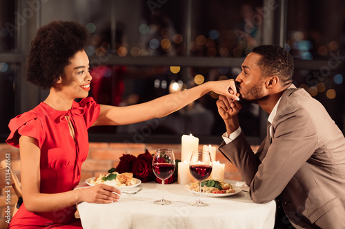 Photographie Man Kissing Woman's Hand Dining In Restaurant Celebrating Valentine's Day