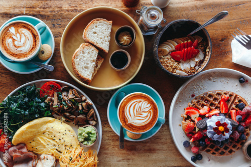 Obraz na płótnie Morning breakfast on a table above, waffles with cream, berries, coffee, cappuccino, bowl, omlet with vegetables, bread with butter, avocado cream, vegan food, healthy food, meal
