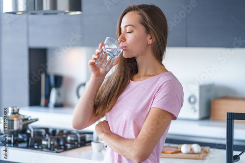 Fotografia Happy attractive joyful brunette woman drinking fresh clean filtered purified water at kitchen at home
