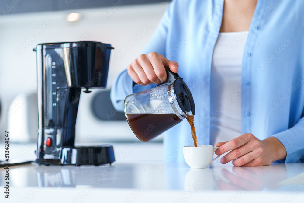 Fototapeta Woman using coffee maker for making and brewing coffee at home. Coffee blender and household kitchen appliances for makes hot drinks
