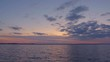 Panorama of a lake or river with dark blue water and beautiful clouds in purple sky during sunset