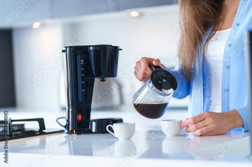 Woman using coffee maker for making and brewing coffee at home Wallpaper Mural