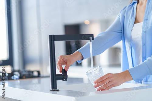 Fotografia, Obraz Female pours fresh filtered purified water from a tap into a glass at kitchen at