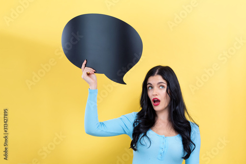 Fotografie, Tablou  Young woman holding a speech bubble on a yellow background