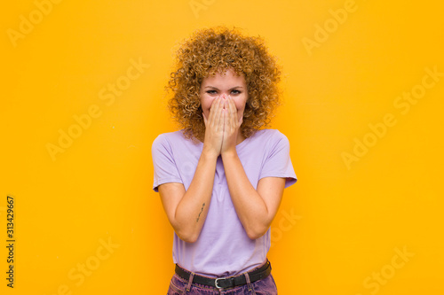 Fotografie, Obraz  young afro woman looking happy, cheerful, lucky and surprised covering mouth wit