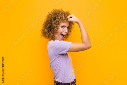 young afro woman feeling happy, satisfied and powerful, flexing fit and muscular Tablou Canvas