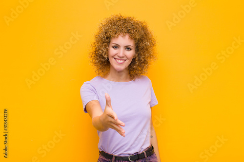young afro woman smiling, looking happy, confident and friendly, offering a hand Canvas Print