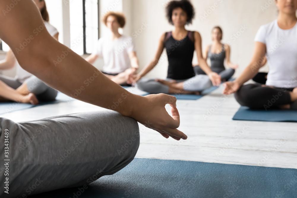 Fototapeta Instructor training diverse people, practicing yoga, doing Lotus exercise