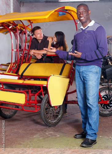 Obraz na plátne Confident cheerful African-American man recommending traveling with rickshaw
