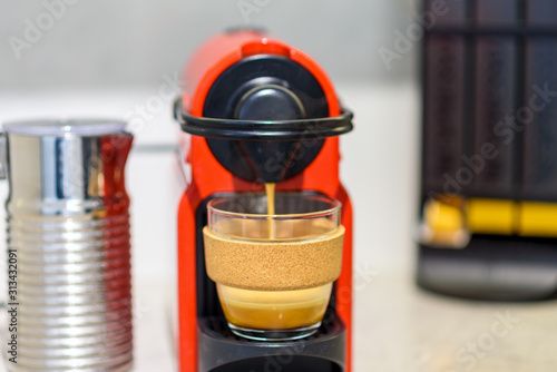Obraz na plátně Coffee machine preparing fresh coffee and pouring into reusable glass coffee cup at restaurant, bar, pub or kitchen