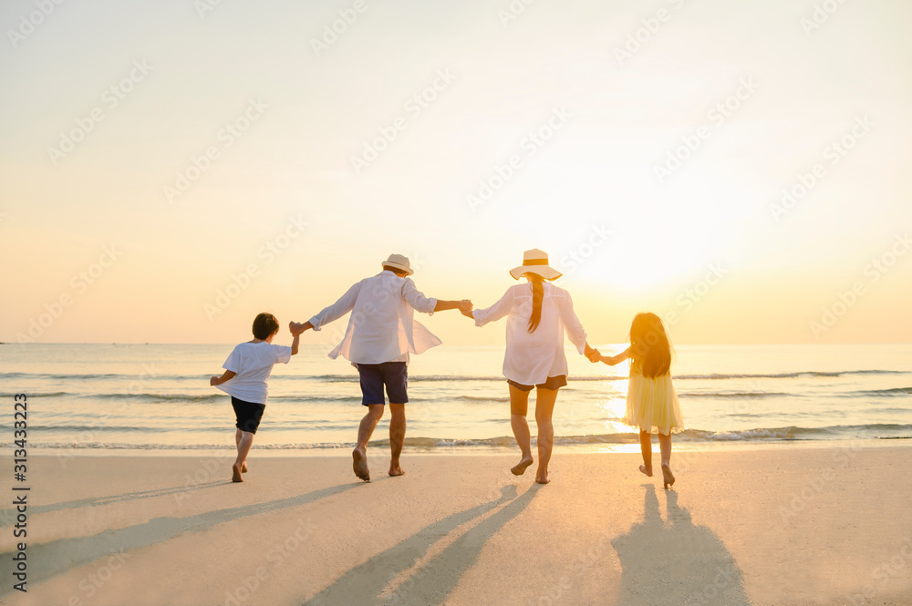Fototapeta Family, travel, beach, relax, lifestyle, holiday concept. Family who enjoy a picnic. Parents are holding hands their children and walking on the beach at sunset in holiday.