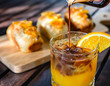 Coffee with orange juice and orange bread on a wooden table