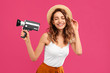 canvas print picture - Beautiful young woman with vintage video camera on crimson background