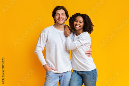 Portrait of smiling mixed-race couple posing over yellow background in studio