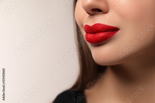 Fototapety, obrazy: Beautiful woman with red lipstick on light background, closeup. Space for text