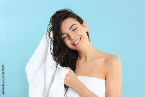 Leinwand Poster Young woman drying hair with towel on light blue background
