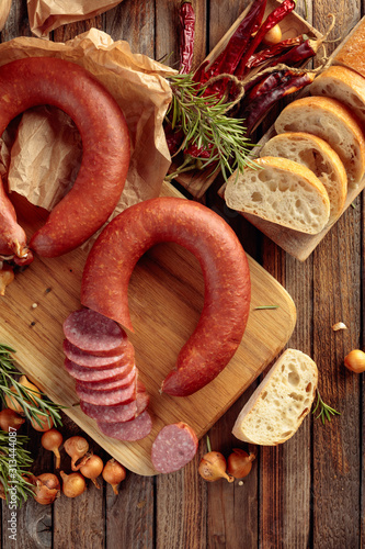 Canvastavla  Smoked sausage with bread and spices on a old wooden table.