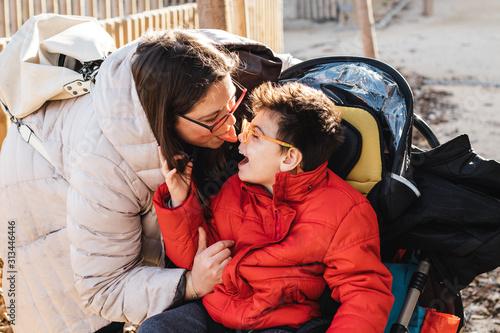 una madre juega con su hijo con pluridiscapacidad en un parque, el niño va con silla de ruedas, es el invierno y van con ropa de abrigo Wallpaper Mural