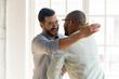 Leinwanddruck Bild - Smiling male friends embrace tap shoulder meeting indoors