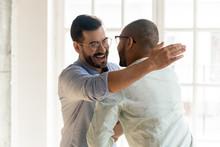 Smiling Male Friends Embrace Tap Shoulder Meeting Indoors