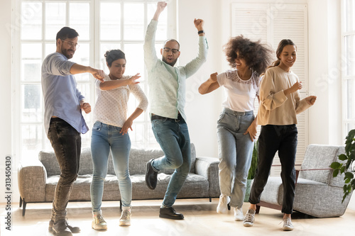 Fotografía Overjoyed multiracial young people dancing together indoors