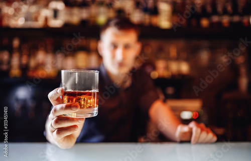 Barman holds out glass of whiskey with ice to male visitor Fototapet