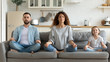 Couple and little daughter sitting on couch do meditation indoors