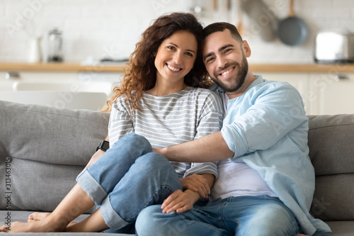 Fototapeta Portrait of couple posing photo shooting seated on couch indoors obraz