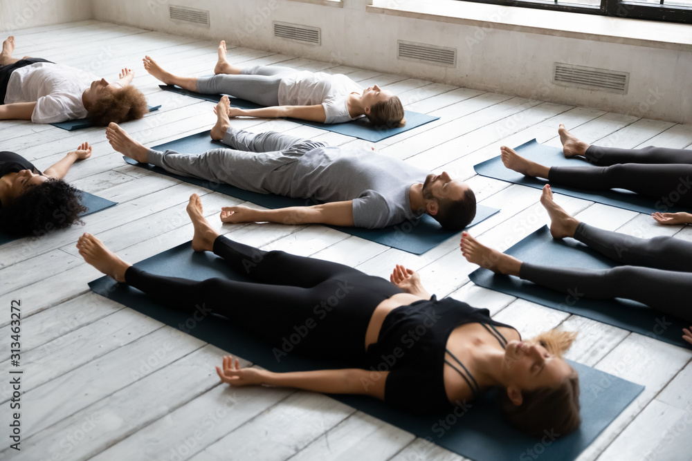 Fototapeta Young people meditating in Savasana pose, practicing yoga at lesson