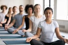 Beautiful Indian Woman Meditating At Group Lesson, Practicing Yoga