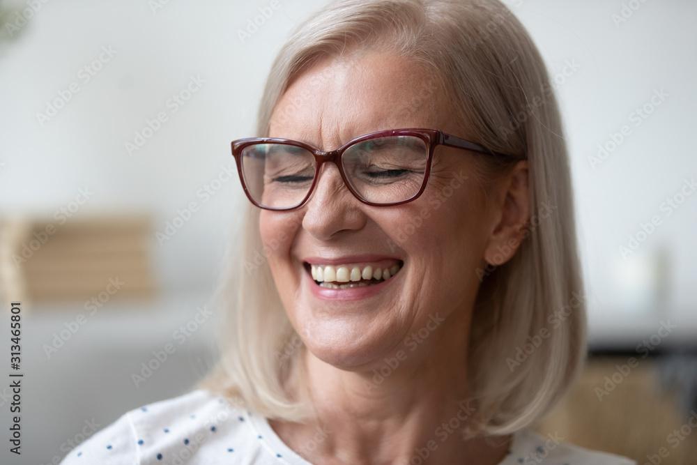 Fototapeta Close up of happy mature woman smiling showing teeth