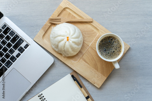 Cup coffee, steamed bun, notepad and laptop on texture white table.