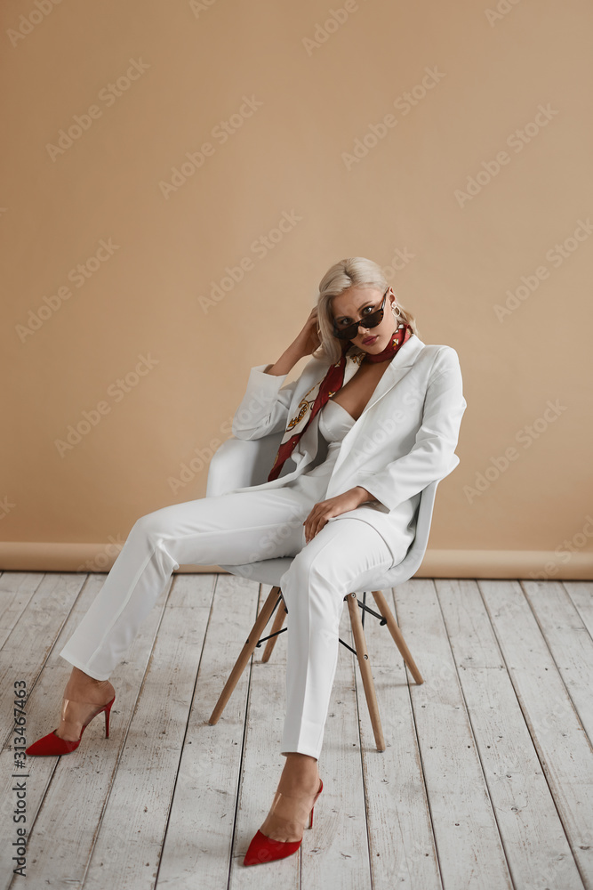 Fototapeta Beautiful young woman with perfect blond hair in elegant white suit and red shoes posing in studio. Fashionable blonde model girl in stylish outfit and sunglasses. Lady boss ready for office meeting