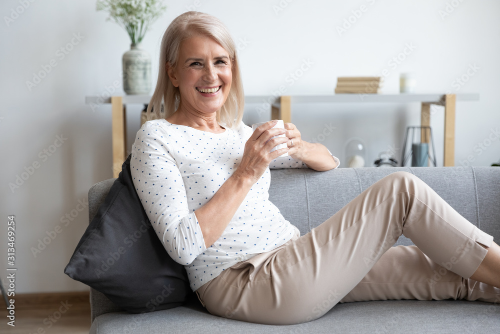 Fototapeta Portrait of smiling mature woman relaxing on couch with cup