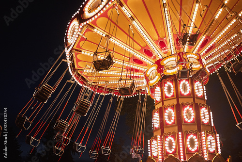 Fototapeta Illuminated swing chain carousel in amusement park at the night