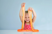 Cute Funny Girl Play With Orange Slime. Kid Squeeze And Stretching Toy Slime.