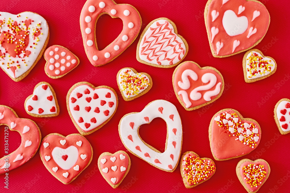 Obraz Background of decorated with icing and glazed heart shape cookies on the red background, flat lay. Valentines Day food concept fototapeta, plakat