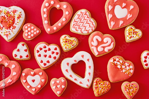 Fototapeta Background of decorated with icing and glazed heart shape cookies on the red background, flat lay. Valentines Day food concept obraz