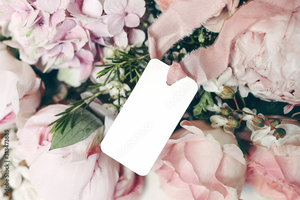 Fototapeta Wedding, birthday stationery mock-up scene. Blank gift tag, label with pink silk ribbon. Decorative floral composition. Closeup of pink roses petals, peonies and hydrangea flowers. Selective focus.