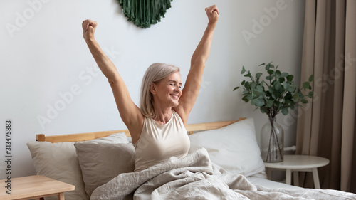 Smiling elderly woman stretching in bed welcoming new day - 313475883